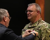 Joseph Schweickert, Director of Human Relations, Illinois National Guard, pins the Meritorious Service Medal to Master Sgt. Philip Squires during his retirement ceremony at Camp Lincoln, Springfield, Illinois, Oct. 30. Squires retired from the Illinois National Guard with 25 years of service. (U.S. Army Photo by Sgt. Stephen Gifford, Illinois National Guard Public Affairs)