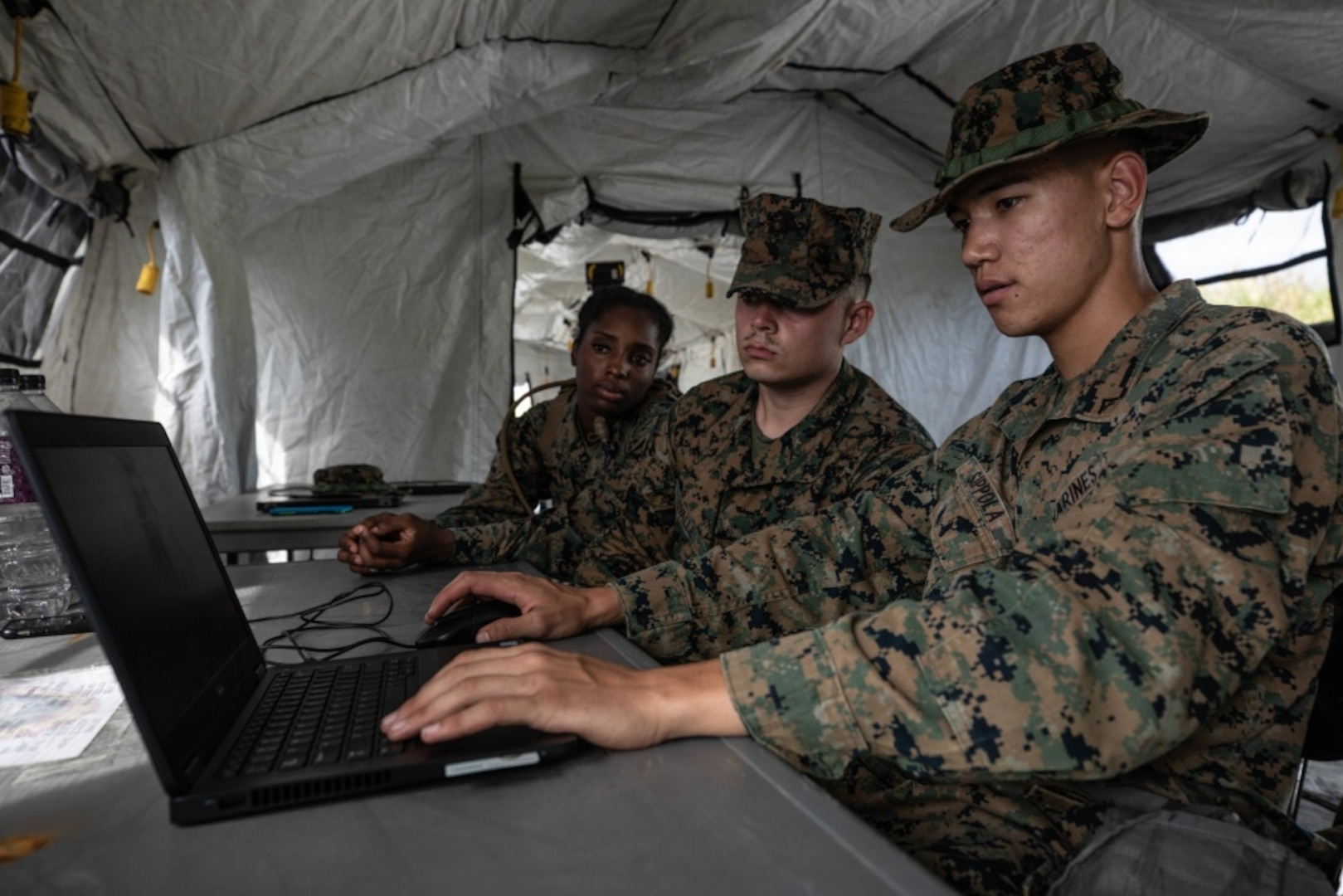 U.S. Marine Corps Lance Cpl. Kinyetta Alfred, left, Lance Cpl. Elijah Ovalle, center, and Lance Cpl. Serik Sippola prepare to ship gear during the 3rd Supply Battalion Marine Corps Combat Readiness Evaluation on Camp Hansen