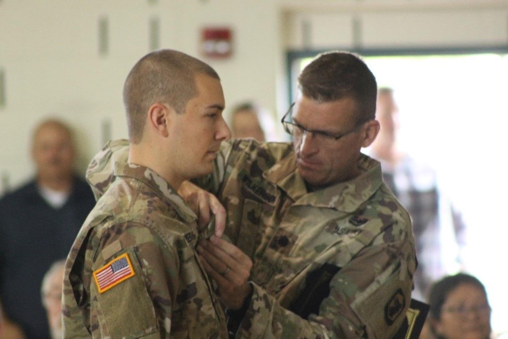 Lt. Col. Justin Wilkerson, of Peoria, Illinois, 404th  Manuever Enhancement Brigade, presents the Illinois National Guard Military Medal of Merit to 2nd Lt. Patrick J. Pendergast, of Plainfield, Illinois. Pendergast, who serves as a platoon leader in the 233rd Military Police Company based in Springfield, Illinois, was awarded the Military Medal of Merit for his contributions to the success of flood response operations during State Active Duty.