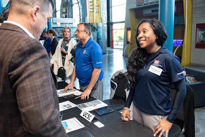 Brandy Wilkerson, a project manager with the Utility Energy Service Contracting program from the U.S. Army Engineering and Support Center, Huntsville, greets an attendee of the 2019 Small Business Forum at the U.S. Space & Rocket Center in Huntsville, Ala., Oct. 24, 2019. The event gave hundreds of business representatives an opportunity to connect face to face with Huntsville Center program and project managers and acquisition professionals.