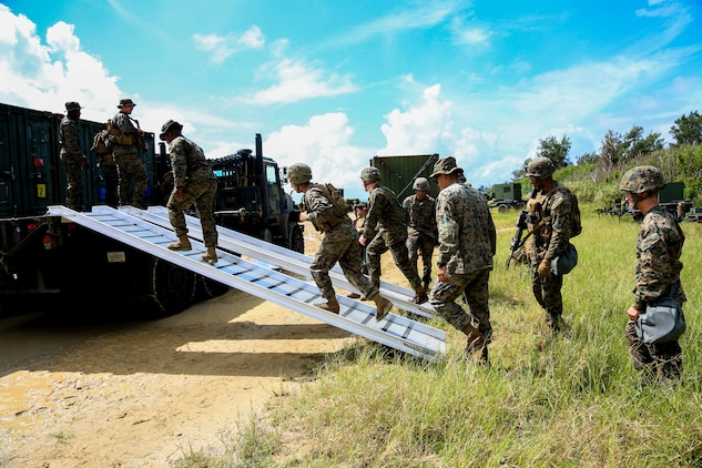 U.S. Marines with Headquarters Battalion, 3rd Marine Division, begin to offload a 7-ton vehicle during Samurai 20-1 on Camp Hansen, Okinawa, Japan, Oct. 22, 2019. The purpose of this exercise is to conduct battle drills that validate the 3rd Marine Division's movement, setup of a combat operations center, force protection, and passage of command and control between supporting elements. (U.S. Marine Corps photo by Sgt. David Staten)