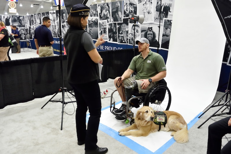 Stacy Pearsall speaking with veteran in wheelchair, photo session