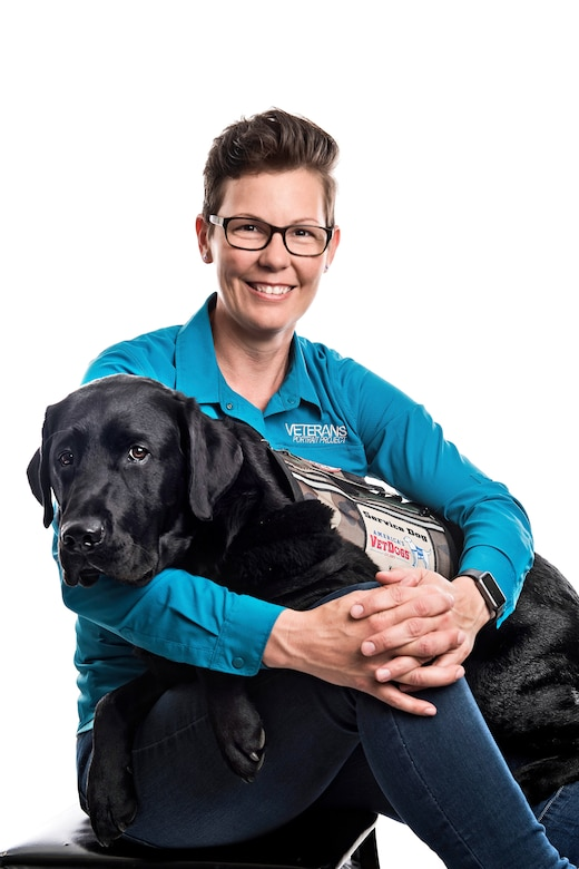 Stacy Pearsall sitting with service dog Charlie on her lap.