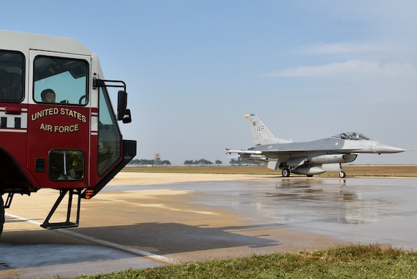 A U.S. Air Force F-16 Fighting Falcon aircraft from the 8th Fighter Wing passes students from the Gunsan Mun Hwa Elementary School during their visit to the 8th Civil Engineer Squadron fire department open house at Kunsan Air Base, Republic of Korea, Oct. 16, 2019. Fire department personnel provided the students with a tour of the fire house, showed them the equipment used to fight fires and taught basic fire safety skills. (U.S. Air Force photo by Tech. Sgt. Joshua Arends)