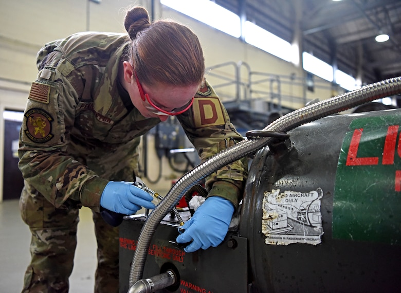 Airman 1st Class Rachael Pennington, 100th Maintenance Squadron aerospace ground equipment technician, lubricates a liquid oxygen tank at RAF Mildenhall, England, Oct. 23, 2019. AGE inspects hundreds of pieces of equipment which are essential to ensuring an aircraft's mission readiness. (U.S. Air Force photo by Senior Airman Brandon Esau)