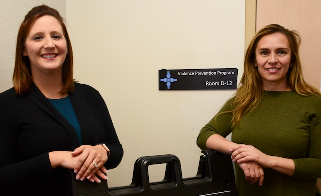 Courtney Sumner, left, and Edith Wegner both with the Violence Prevention Program, pose for a photo at their office during Domestic Violence Awareness Month, Oct. 29, 2019. The Air Force-wide Violence Prevention Program, in its second year, uses strategies and training from the Sexual Assault Prevention and Response Program and the Suicide Prevention Program. (U.S. Air Force photo by Jessie Perkins)