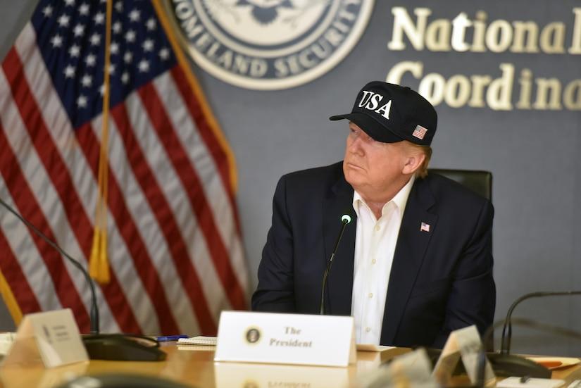 President Trump, wearing a black USA baseball cap, listens during a briefing.