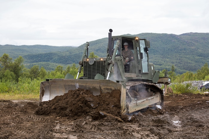 A U.S. Marine with II Marine Expeditionary Force, uses a medium crawler tractor to move rocks during a heavy equipment operation in Setermoen, Norway, Aug. 22, 2019.