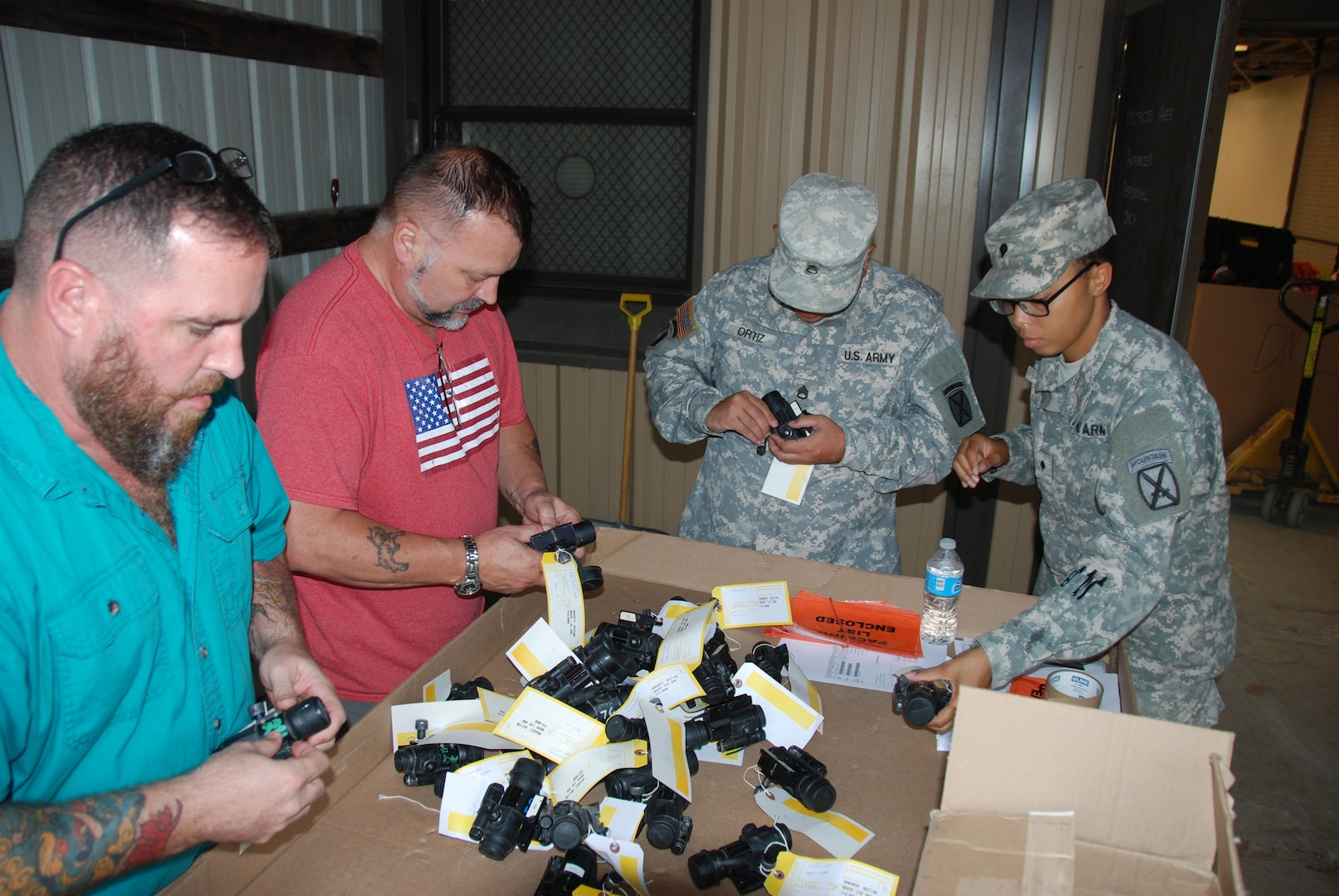 Two soldiers and two civilians checking over excess equipment ready for turn-in.