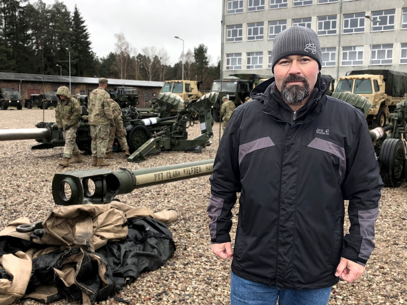 Photographic illustration of Customer Support Representative in front of military personnel preparing large scale equipment in a gravel parking lot.