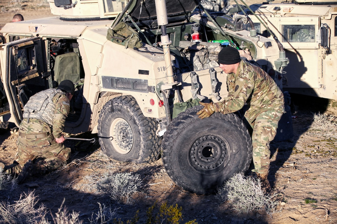 Two soldiers changing a tire on a Humvee.