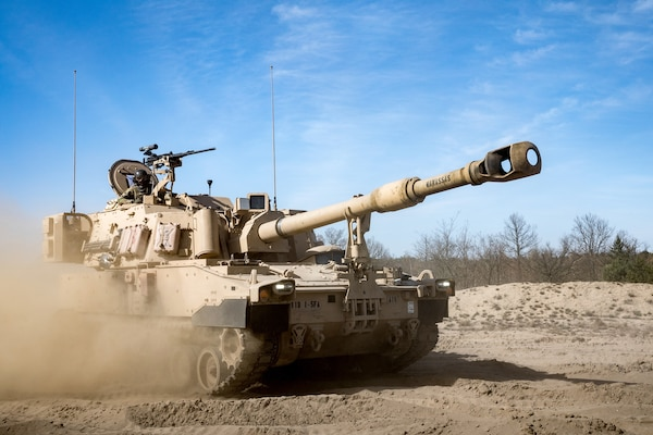 Paladin howitzer travels on dirt road kicking up a trail of dust.