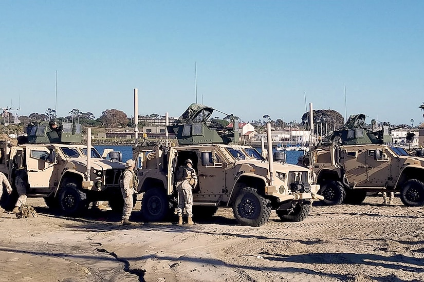 Long shot image of 3 Humvees with 2 Marines checking over the vehicles.