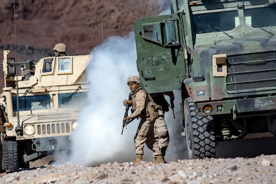 Image of a Marine exiting a green cammo truck with a smoke cloud behind it and a Humvee in the background.