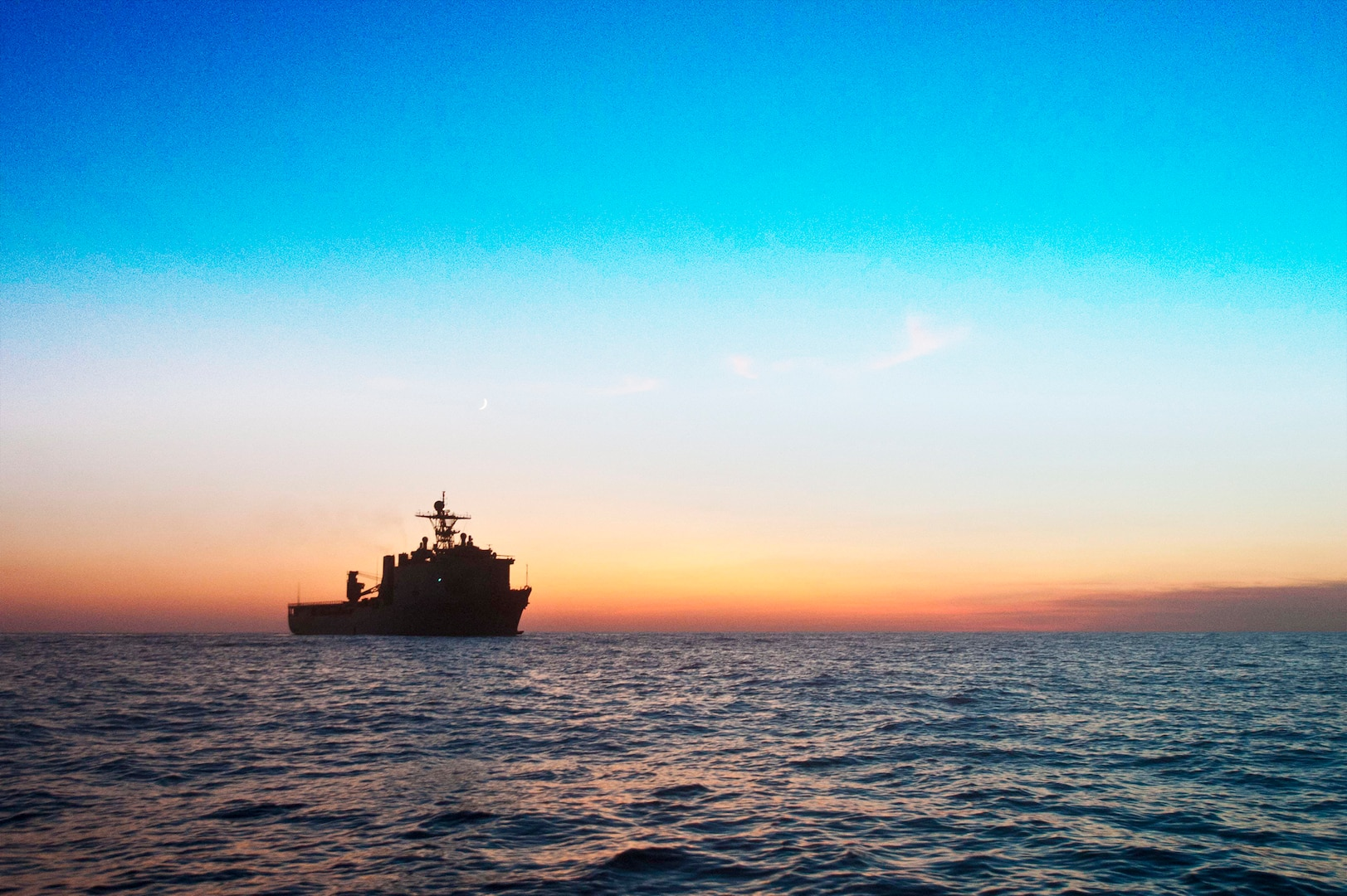 Image of ocean view at sunset on the horizon with USS Fort McHenry in the distance.