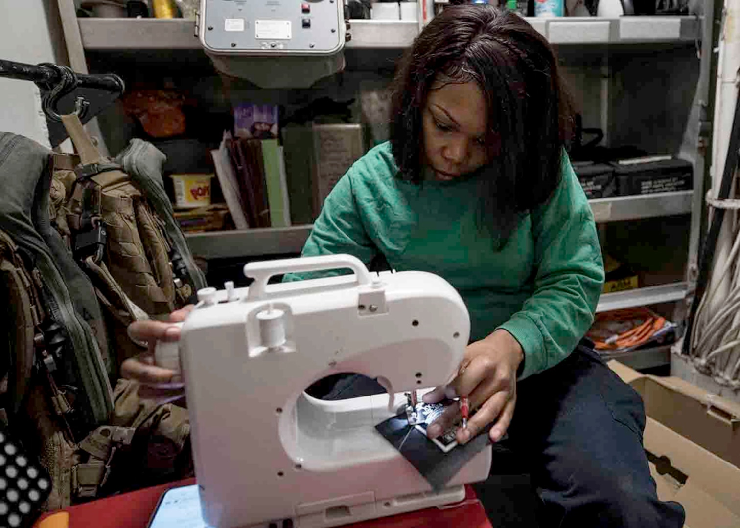 Image of female sailor using a sewing machine