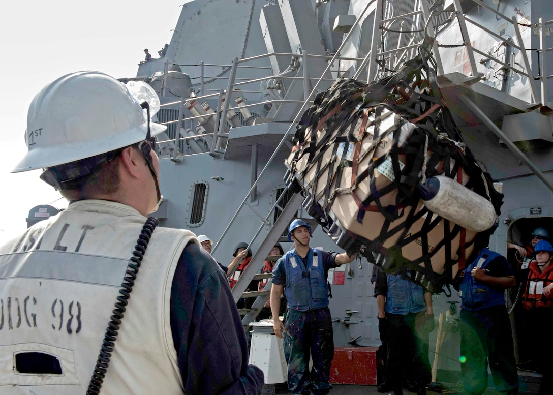 Image of sailors onboard a ship using a hook lift a cargo net of supplies.