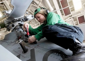 Image of a sailor leaning under stationary helicopter rotor while working on repairs.