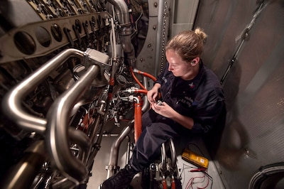 Image of a female sailor inside an engine compartment performing maintenance.