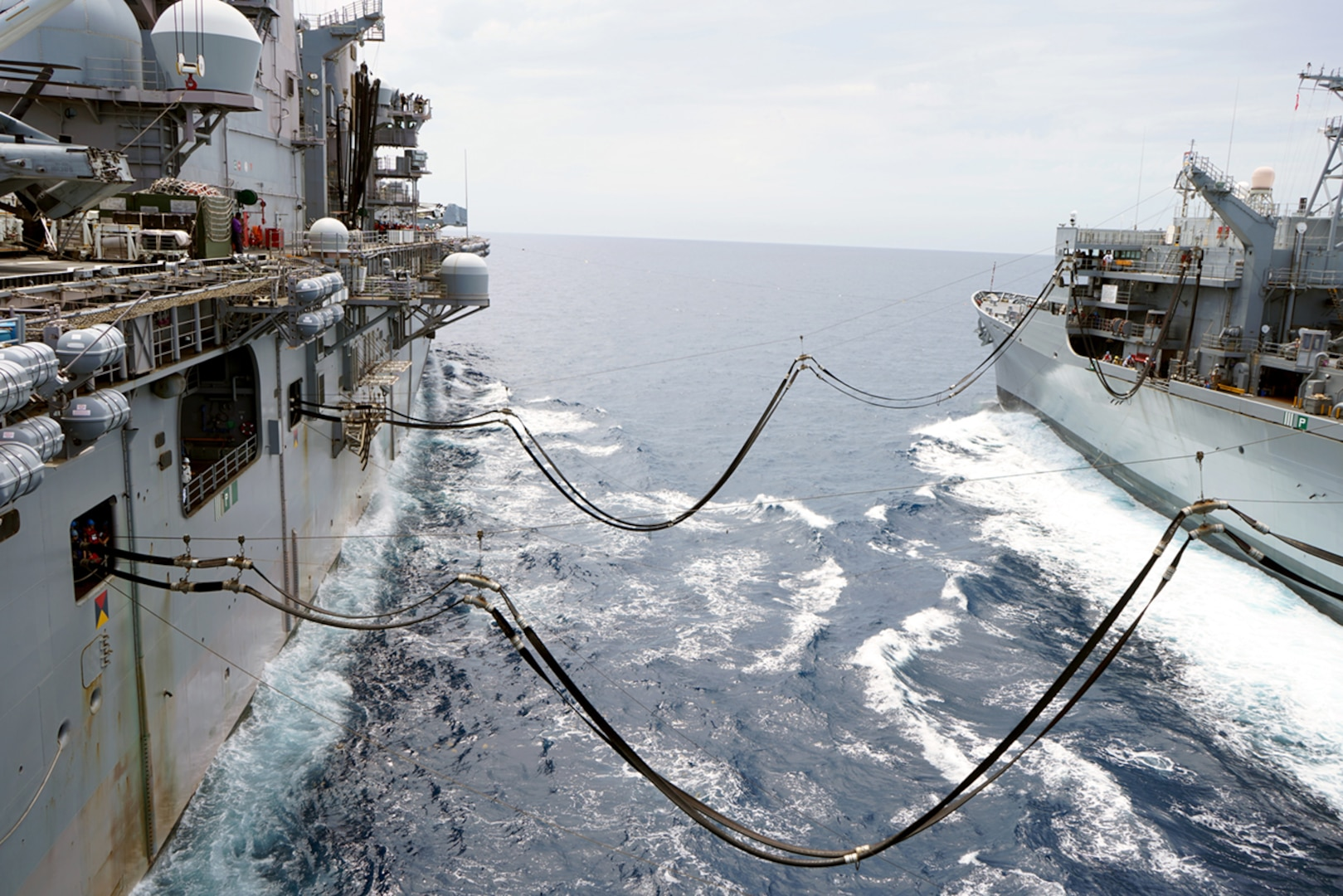 Image of two navy ships at sea with fuel resupply lines running between the two ships.
