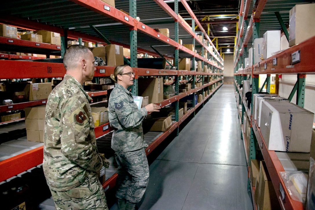 Image of two Air Force personnel with large warehouse shelving units extending back to the warehouse wall.