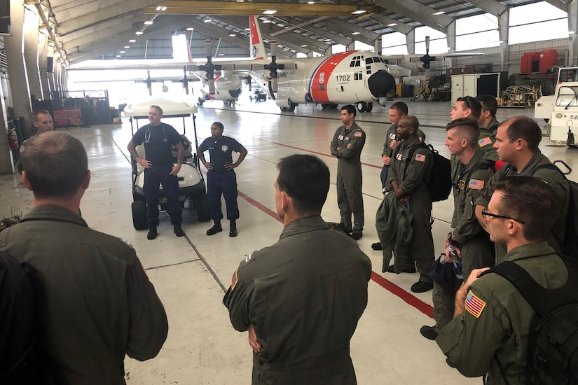 A group of service members listen to a briefing in an airplane hangar.