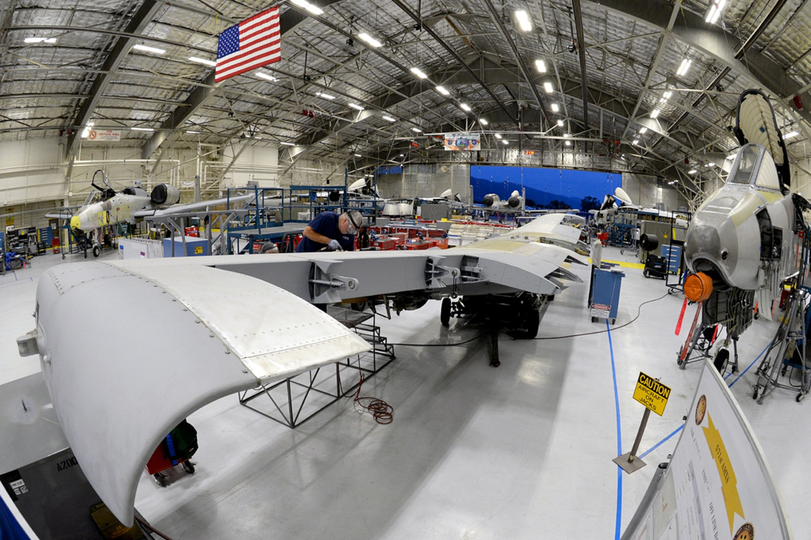 Wide-angle image of maintenance facility with mechanic working on an aircraft wing.