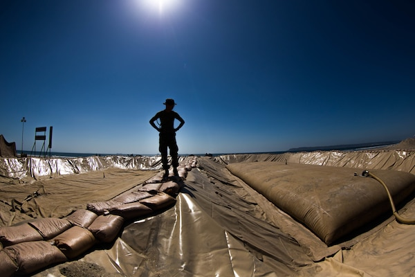 Image of a fuel pit with sandbags for walking, silhouette of Marine standing with fuel bladder being filled to the right, deep blue sky above.