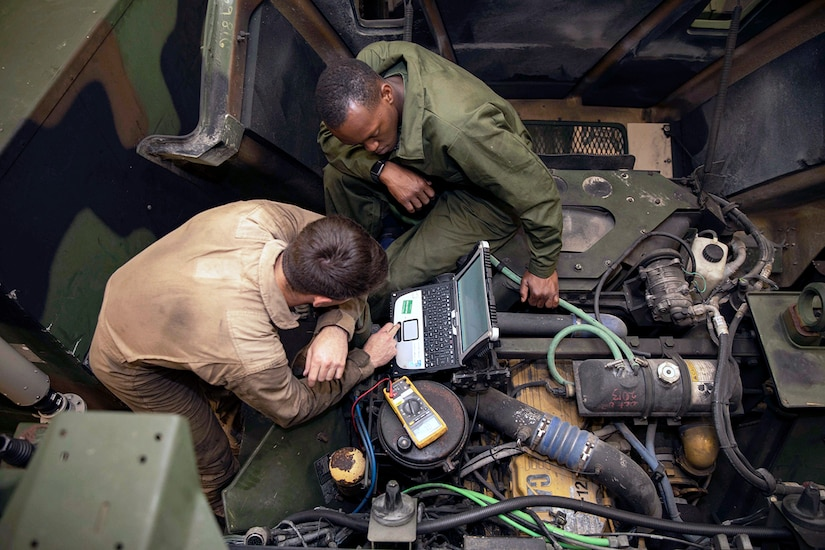 Image of two mechanics in Medium Tactical Vehicle Replacement compartment using a computer with multiple tubes and hoses and electronic meter system.