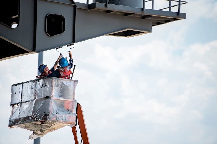 Image of two sailors in a lift bucket painting the underside of an extended part of a ship's hull.