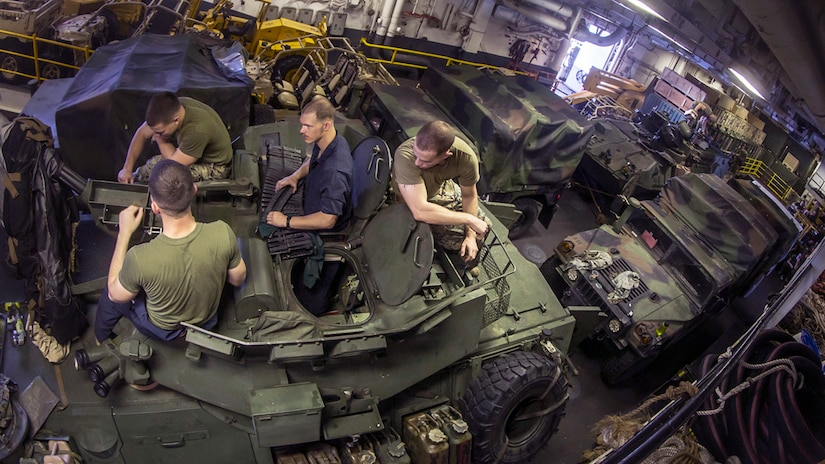 Image of four Marines sitting on top of a light armored vehicle, with other vehicles extending to the back of the ship's hold compartment.