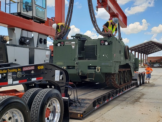 Civilian-Marines and Defense Logistics Agency employees load an M9 Armored Combat Earthmover at Marine Corps Logistics Base Albany.  Marine Corps Logistics Command and DLA worked together to ship several M9 combat excavators in order to serve training needs in California and Nevada.