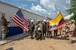 U.S. Navy Seabees and Colombian army engineers pose with their national flags.