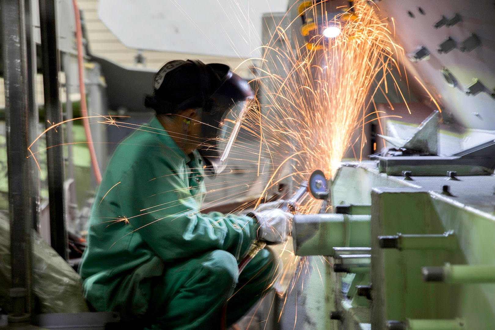Image of a welder with a angle grinder with sparks coming off the metal plate he's working on.