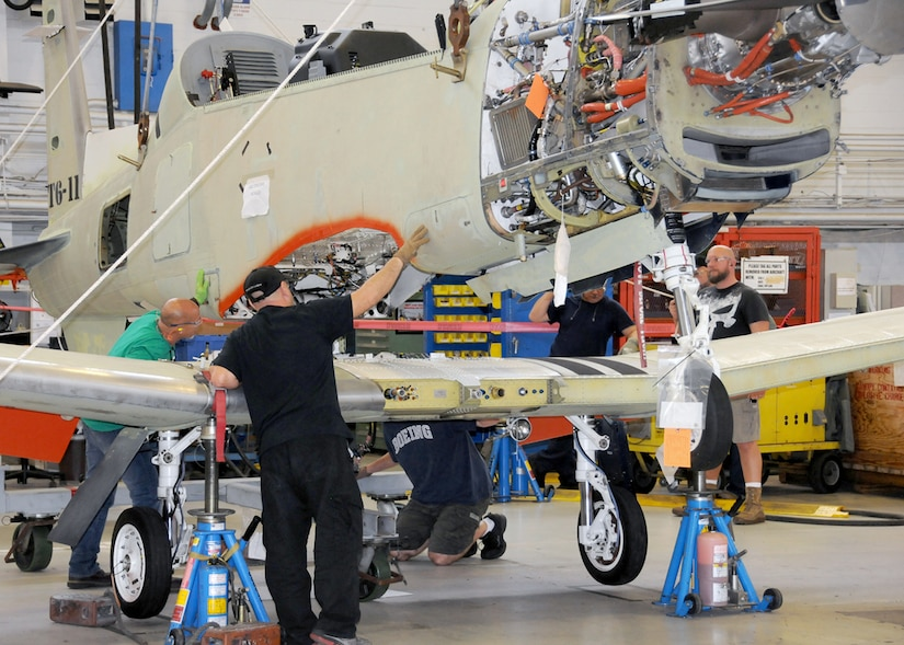 Image of four workers placing wing assembly onto airplane body.