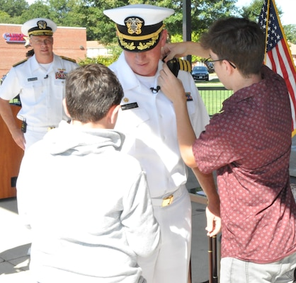 IMAGE: DAHLGREN, Va. (Aug. 30, 2019) – Quinn and Elijah Plew attach new shoulder boards on their father, Capt. Casey Plew, during his promotion ceremony at Naval Surface Warfare Center Dahlgren Division (NSWCDD). It was Plew's second ceremony marking a career milestone in four months. The new Navy captain took command of NSWCDD – the Naval Sea System Command's largest Naval Warfare Center – at a ceremony held on the Potomac River Test Range in April.