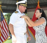 IMAGE: DAHLGREN, Va. (Aug. 30, 2019) – Carolina Plew pins a new name tag on her husband, Capt. Casey Plew, during his promotion ceremony at Naval Surface Warfare Center Dahlgren Division (NSWCDD). It was Plew's second ceremony marking a career milestone in four months. The new Navy captain took command of NSWCDD – the Naval Sea System Command's largest Naval Warfare Center – at a ceremony held on the Potomac River Test Range in April.