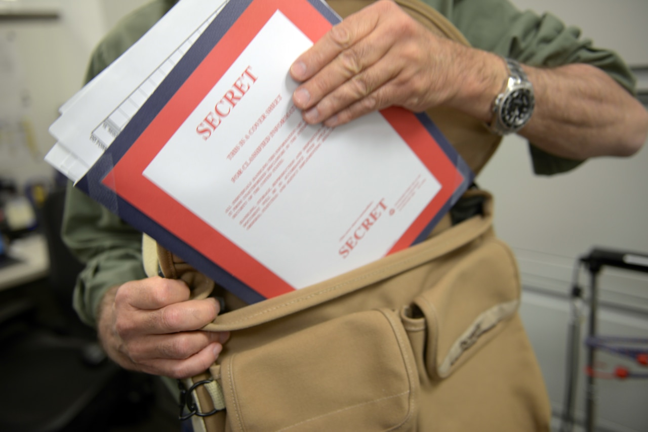 "A hand places a folder with a ""SECRET"" cover sheet into a messenger bag."