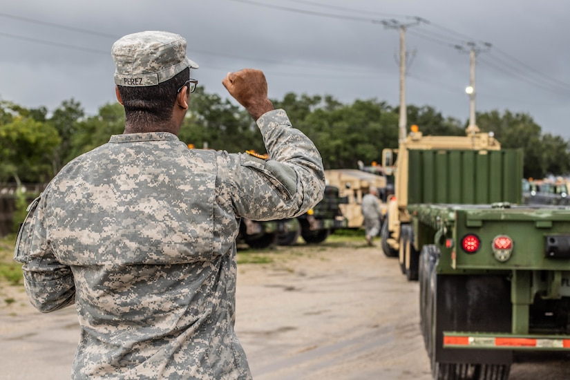 A soldier holds up his fist to signal a truck driver out of frame.