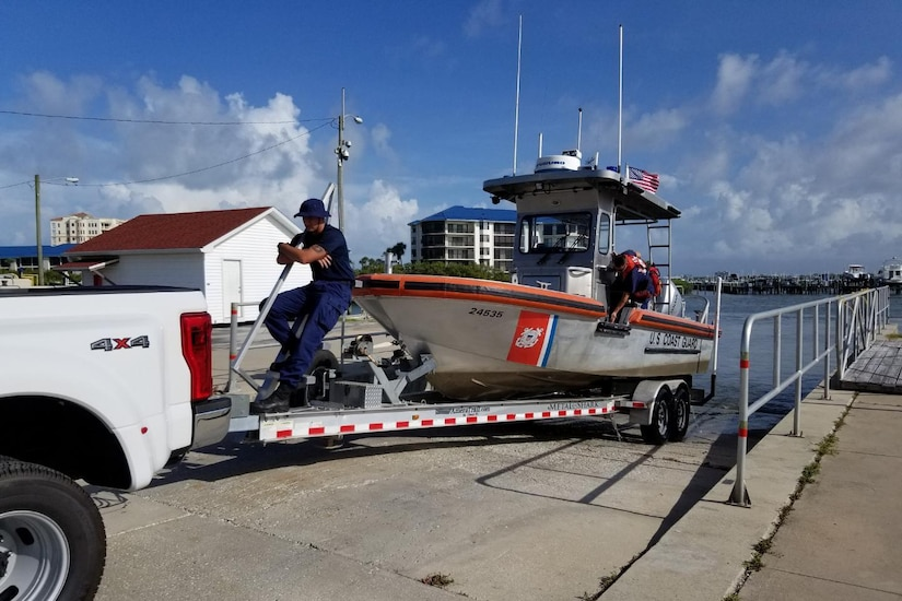 A Coast Guardsman rides on the bow of a boat being towed by a pickup truck.
