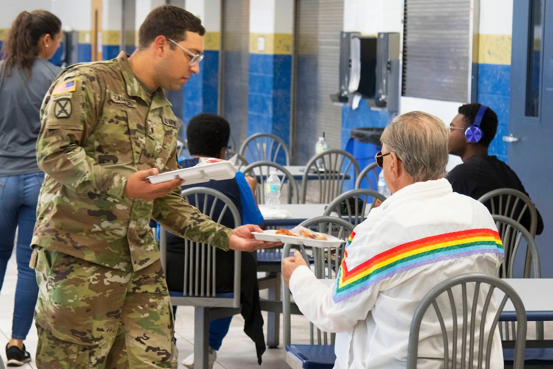 A soldier hands a plate of food to a man sitting in a cafeteria-type facility.