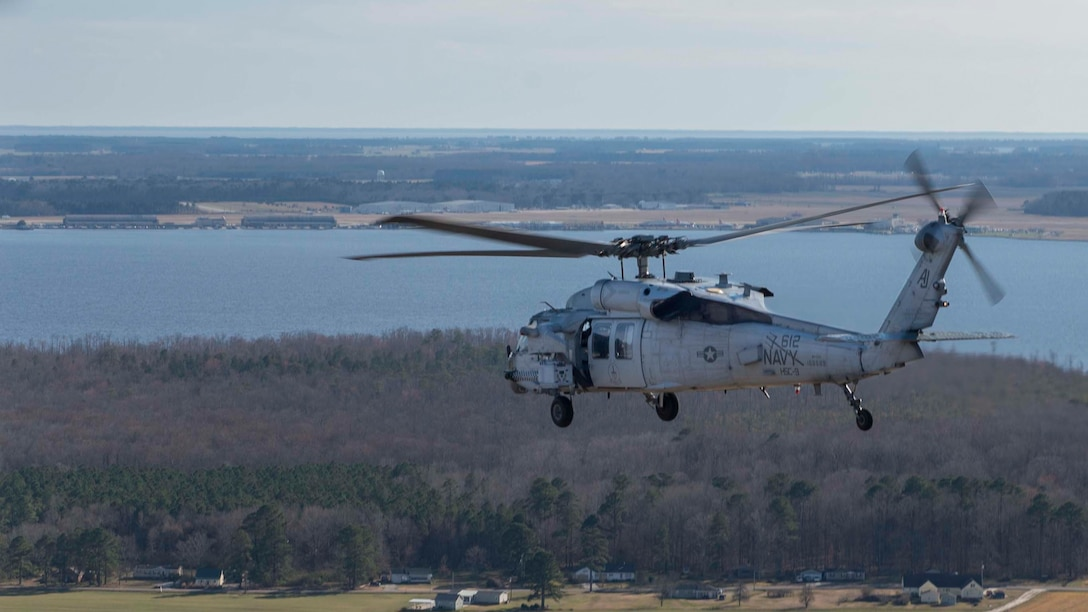 A helicopter flies over rural terrain. In the far background is a large body of water.