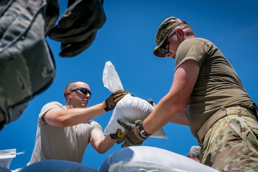 Looking upward towards a clear, blue sky, service members pass sandbags to one another.