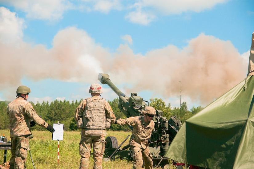 Three service members shoot a howitzer into the air on a bright day with a blue sky. Smoke can be seen coming from the end of the barrel.