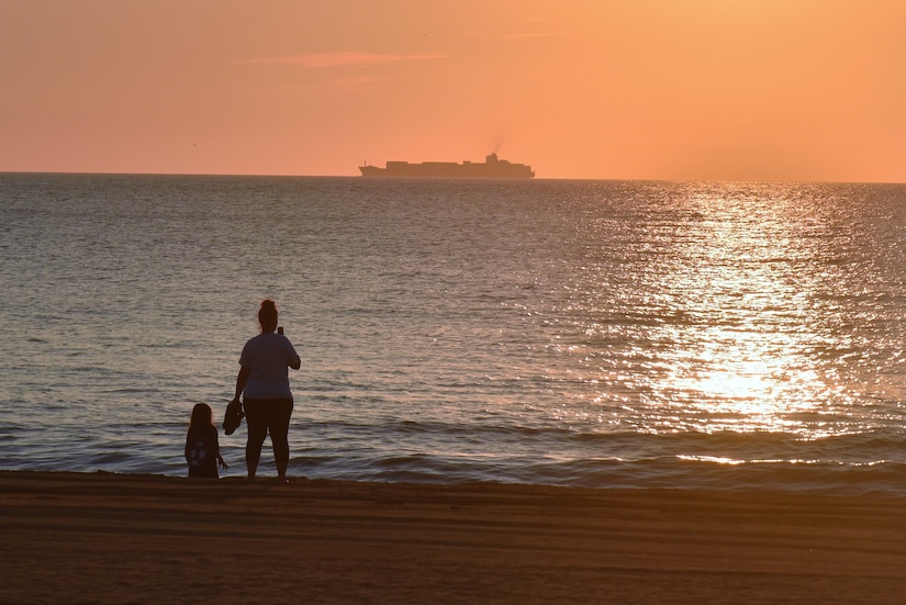 Mother and daughter on the beach watch a ship out in the ocean at sunrise
