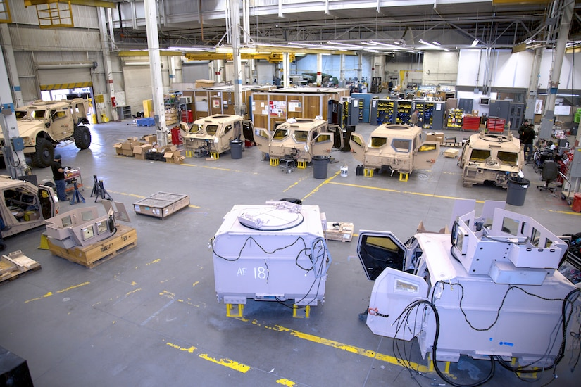 Image of warehouse action with MRAP parts placed in bays.