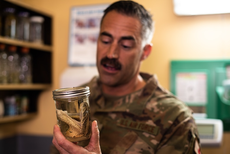 U.S. Air Force Maj. William White, 475th Expeditionary Air Base Squadron senior medical officer, explains the different types of wildlife found in the surrounding area to 435th Air Expeditionary Wing leadership during an immersion tour at Camp Simba, Kenya, Aug. 30, 2019. White showed the wing commander and command chief which types of snakes require immediate medical attention. (U.S. Air Force photo by Staff Sgt. Devin Boyer)