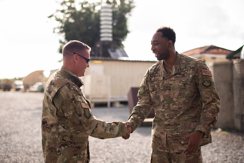 U.S. Air Force Col. Daniel C. Clayton, 435th Air Expeditionary Wing and 435th Air Ground Operations Wing commander, coins Tech. Sgt. Dominique Barrett, 475th Expeditionary Air Base Squadron personnel support for contingency operations, during an immersion tour at Camp Simba, Kenya, Aug. 30, 2019. Clayton, and Chief Master Sgt. Jeremy Unterseher, 435th AEW and 435th AGOW command chief, visited each location in the area of responsibility as part of an immersion tour. (U.S. Air Force photo by Staff Sgt. Devin Boyer)