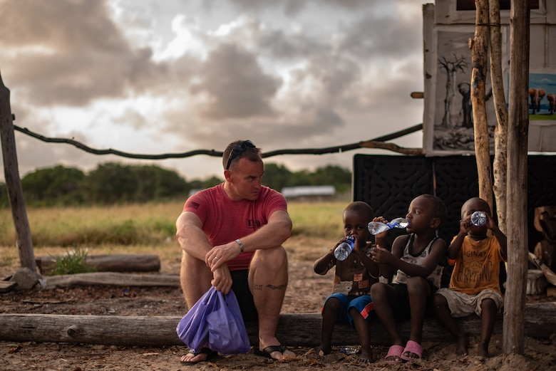 U.S. Air Force Chief Master Sgt. Jeremy Unterseher, 435th Air Expeditionary Wing and 435th Air Ground Operations Wing command chief, talks to children at a village near Camp Simba, Kenya, Aug. 30, 2019. Unterseher and Col. Daniel C. Clayton, 435th AEW and 435th AGOW commander, visited the village as part of an immersion tour for the 435th AEW. (U.S. Air Force photo by Staff Sgt. Devin Boyer)