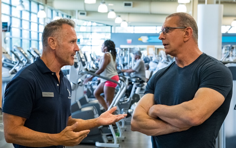 John Walters (left), 436th Force Support Squadron fitness program manager, speaks with chef Robert Irvine about the equipment and programs offered at the Fitness Center, Aug. 27, 2019, at Dover Air Force Base, Del. After a brief tour, Irvine taught Team Dover members about healthy eating and cooking during a Dorm to Gourm session. (U.S. Air Force photo by Roland Balik)